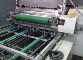 Скоба механізму подавання віконець для вклеювання в упаковку машини для вклеювання віконець «Heiber & Schroeder WP 800D» (вказано стрілкою)